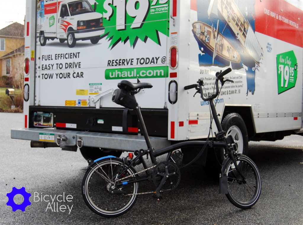 The Brompton bicycle unfolded and leaning against the U-haul 10 foot moving truck.