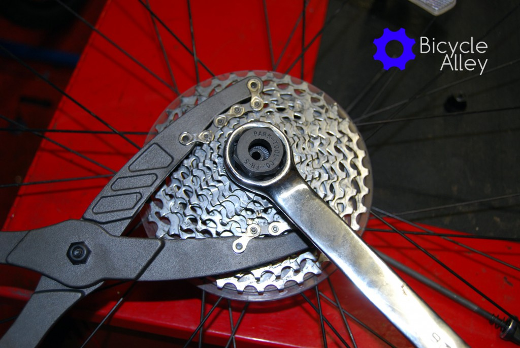 The 10 speed cassette being held by the Park Tools CP-1 pliers, and a 26mm wrench turning the Park Tools FR-5 lockring tool.
